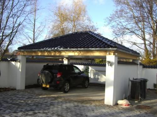 Valmcarport til to biler med synlige umalede limtræsremme og glaseret tegl