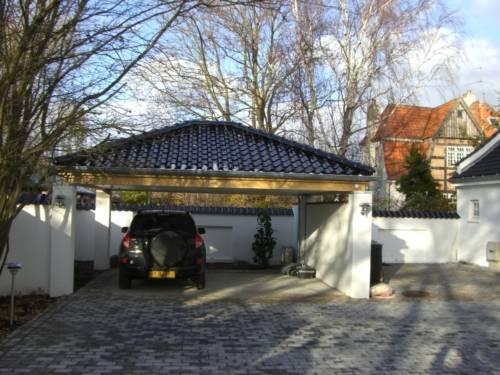 Løsning med murede søjler, umalede limtræsremme samt sort tegltag