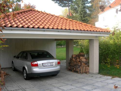Carport med valm og rødt tegltag. Murede søjler, samt limtræsremme