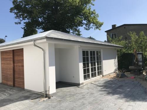 Garage med foldedør samt skydedør med mahogni listedækning